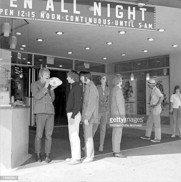 Supergroup 'Buffalo Springfield' perform pose for a portrait outside a movie theatre in 1966 in Hollywood California Dewey Martin Richie Furay Neil...