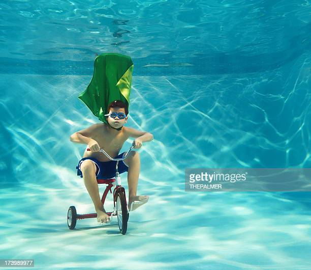 superhero boy riding a tricycle underwater