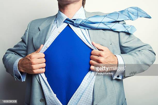 Superhero Businessman in Blue T-Shirt Pulling Suit Open