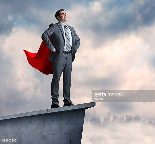 Superhero businessman standing on promontory with city in distance