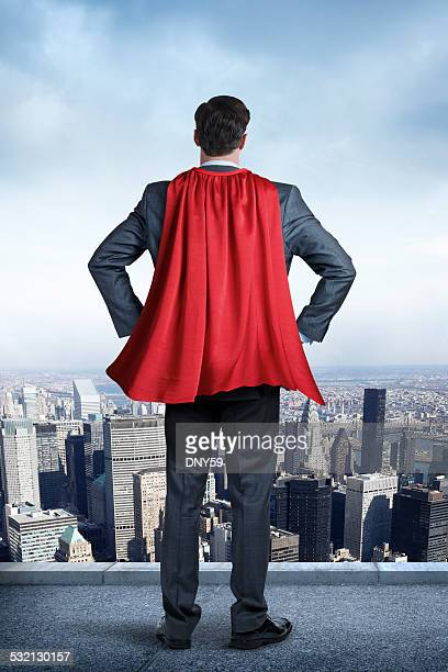 Superhero Businessman Wearing Red Cape Looking At Big City