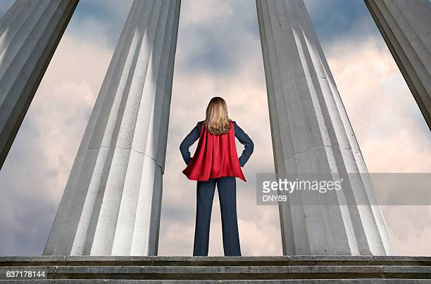 superhero businesswoman standing among tall columns - cape garment stock photos and pictures