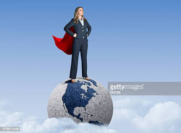 Superhero Businesswoman Standing On Globe