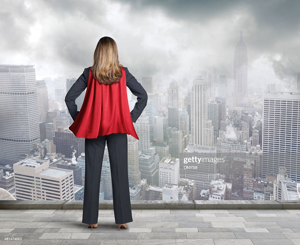 Superhero Businesswoman Wearing Red Cape Looking At Big City : Stock Photo