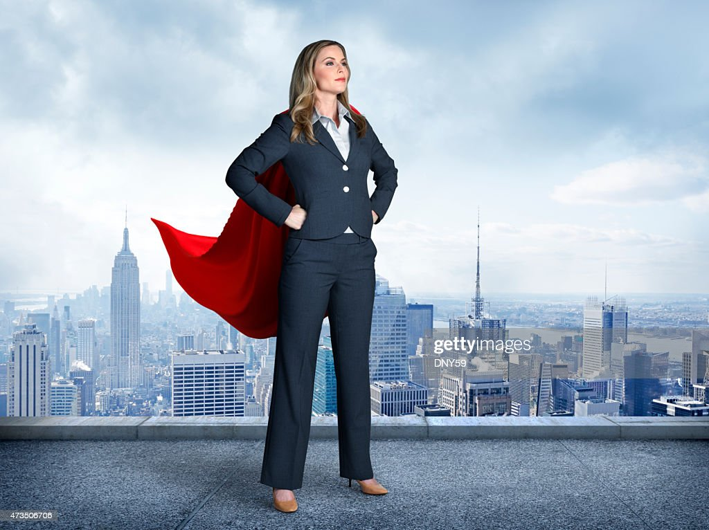 Superhero Businesswoman With Cityscape In The Background : Stock Photo