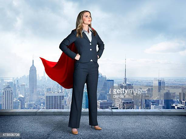 superhero businesswoman with cityscape in the background - handen op de heupen stockfoto's en -beelden