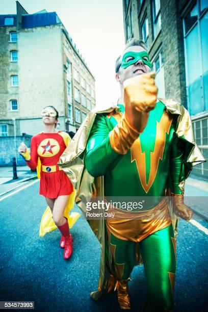 Superhero couple running on city street