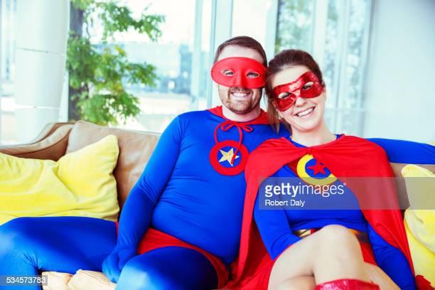 Superhero couple smiling on living room sofa
