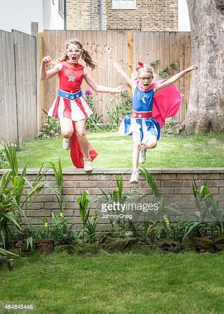 Superhero girls leaping off wall in garden