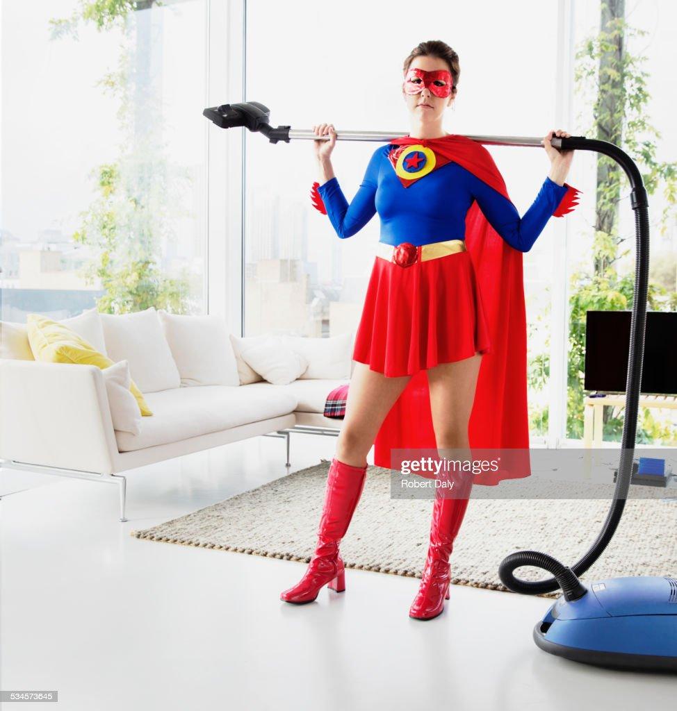 Superhero holding vacuum in living room : Stock Photo