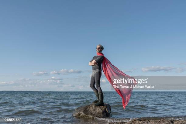 superhero jumps from a rock into the water. germany. - schleswig holstein stock photos and pictures