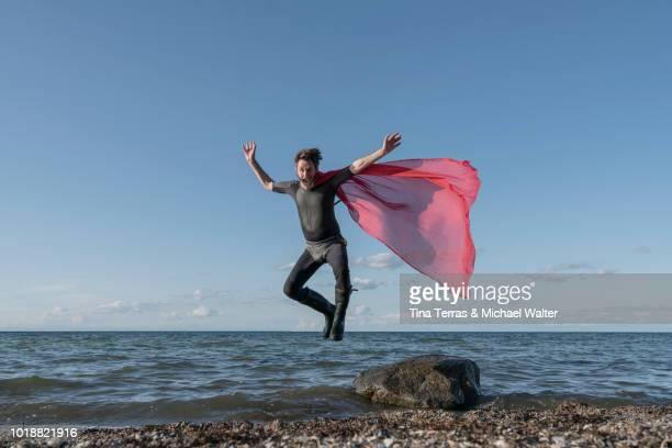 superhero jumps from a rock into the water. germany. - offbeat stock photos and pictures
