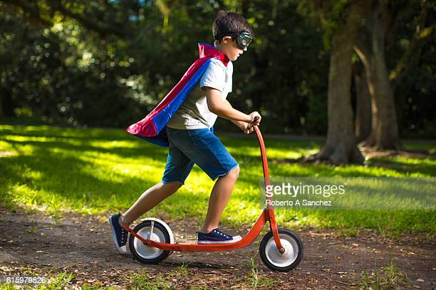 Superhero kid on scooter