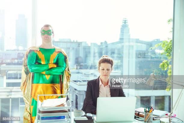 Superhero standing near businesswoman working in office