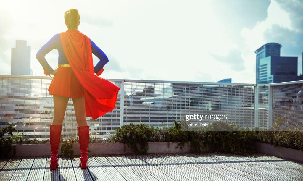 Superhero standing on city rooftop : Stock Photo