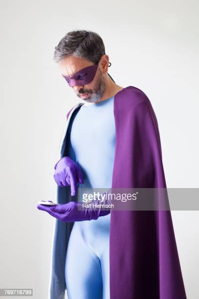 Superhero using smart phone while standing against white background