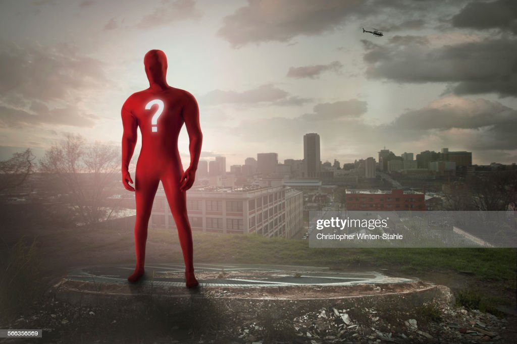 Superhero with question mark costume overlooking cityscape : ストックフォト