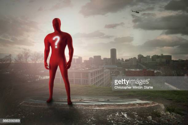 Superhero with question mark costume overlooking cityscape