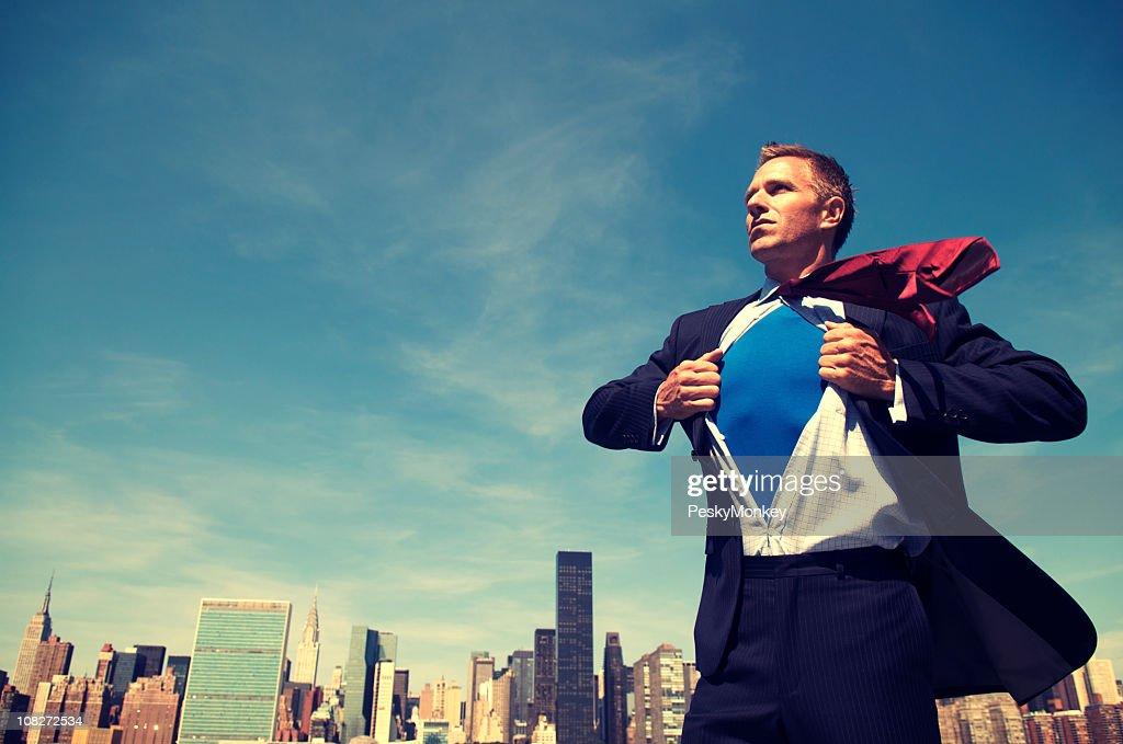 Superhéroe joven hombre de negocios de pie al aire libre con vista a la ciudad : Foto de stock