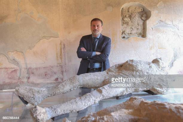 Superintendant Massimo Osanna poses near pietrified victims of the eruption of Vesuvius Volcano are displayed in the House of Siricus