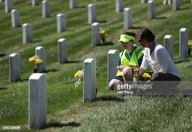 Superintendent of Arlington National Cemetery Kate Kelley and Jenna Gilbey of Elkridge Maryland read the name on a tombstone after they placed...