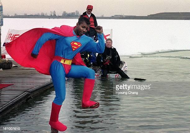 Superman David Clark of Denver jumps into Boulder Reservoir for Annual Boulder Polar Bear Club's New Year's Day Ice Swim on Monday