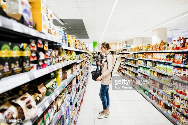 supermarket aisle with people grocery shopping - winkelen stockfoto's en -beelden