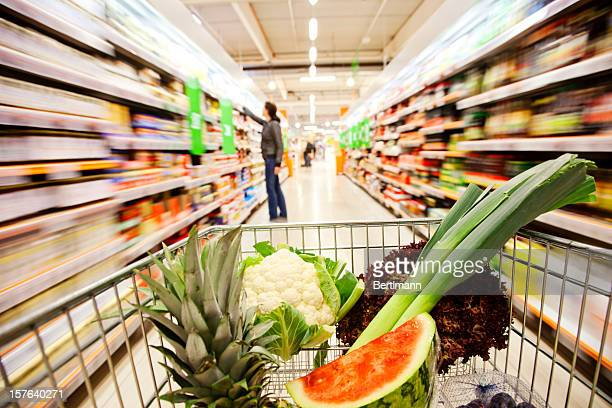 Supermarket cart filled with fresh fruit and vegetables