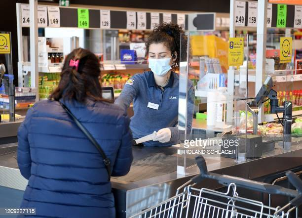 Supermarket cashier wears a face protection in Vienna on April 6, 2020. - As of today, April 6 it is mandatory in Austria to wear face protection in...