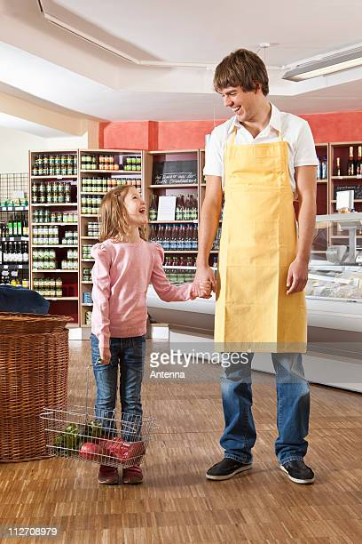 A supermarket clerk laughing with a young girl