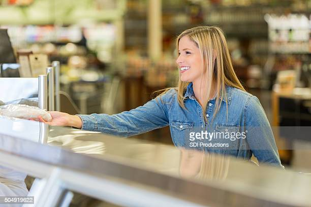 Supermarket customer buying meat from deli counter in supermarket