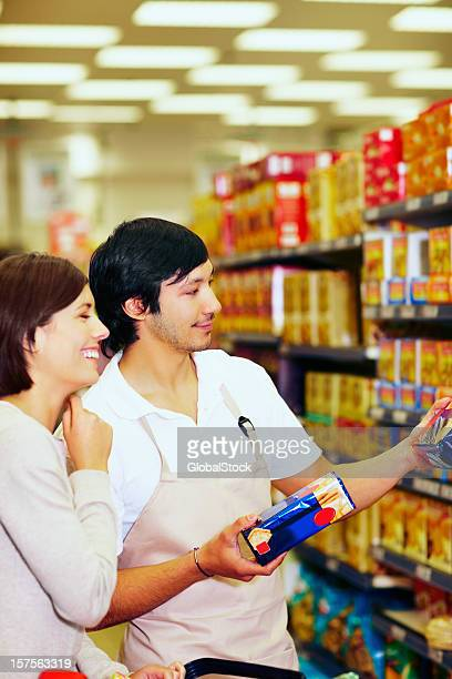 Supermarket employee assisting a customer with the products