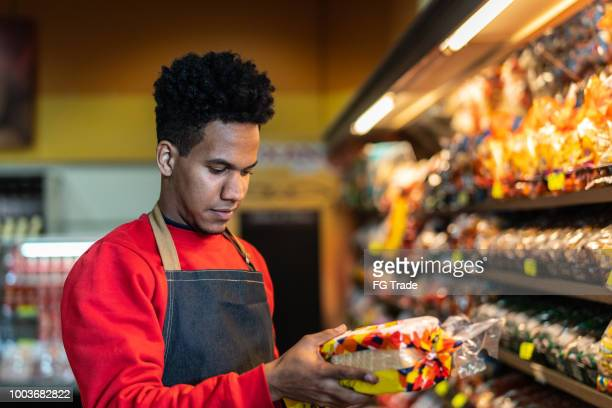 supermarket employee checking bread shelf life in the bakery - consumerism stock pictures, royalty-free photos & images