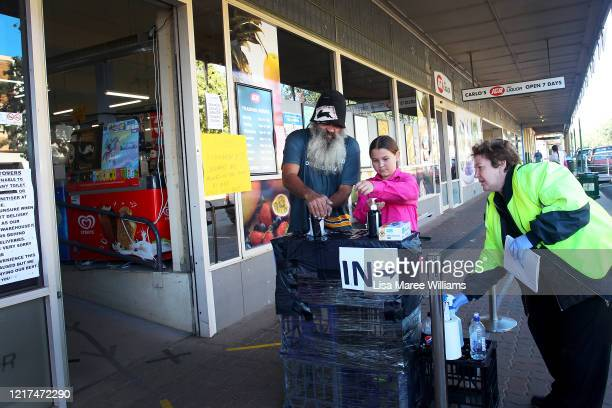 Supermarket employee directs shoppers to sanitise their hands and apply social distancing in-store on April 06, 2020 in Manilla, Australia. The...