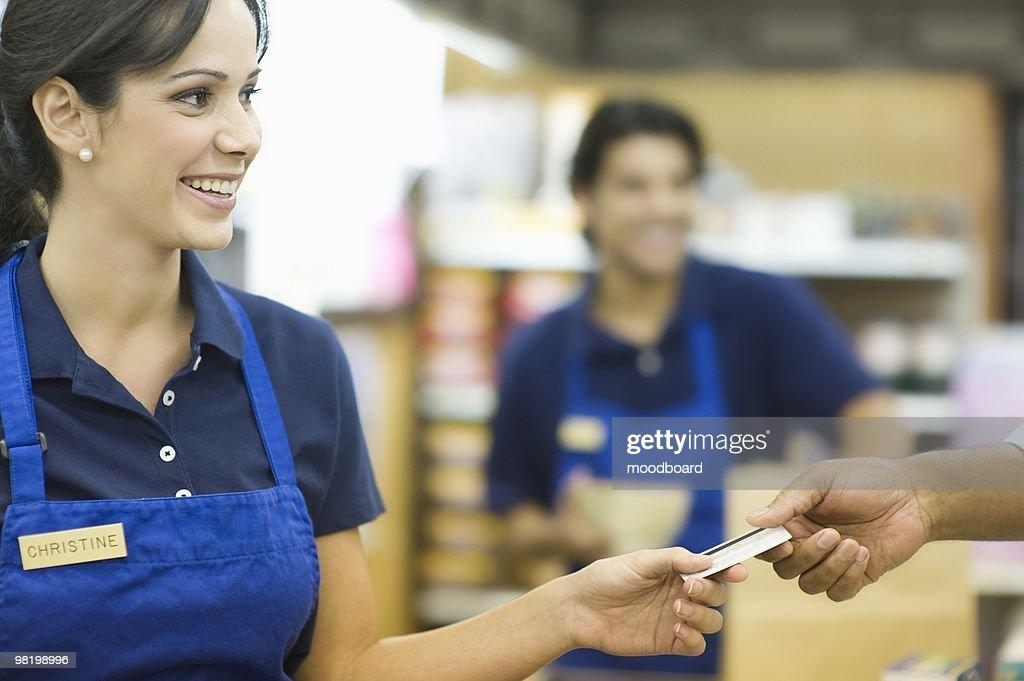 Supermarket employee in blue apron : Stock Photo