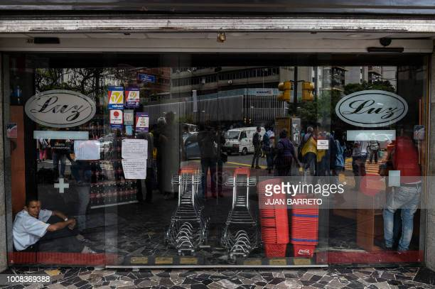 A supermarket employee rests behind a window during a power cut in Caracas on July 31 2018 A power failure cut electricity to 80 percent of the...