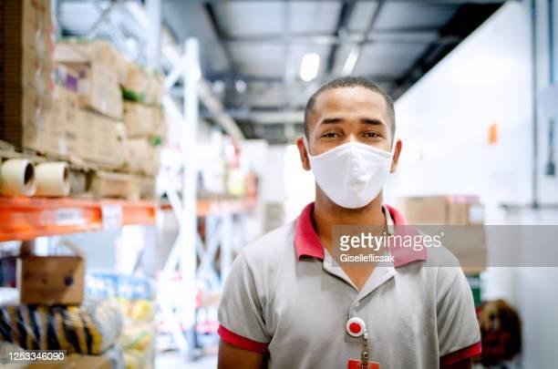supermarkt-mitarbeiter mit einem tablet, um lager zu überprüfen - essenzielle berufe und dienstleistungen stock-fotos und bilder