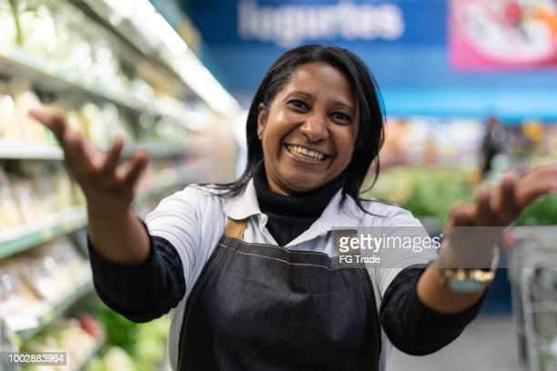 empleado de supermercado mujer haciendo señas - invitando a clientes a venir - mercado espacio de comercio fotografías e imágenes de stock