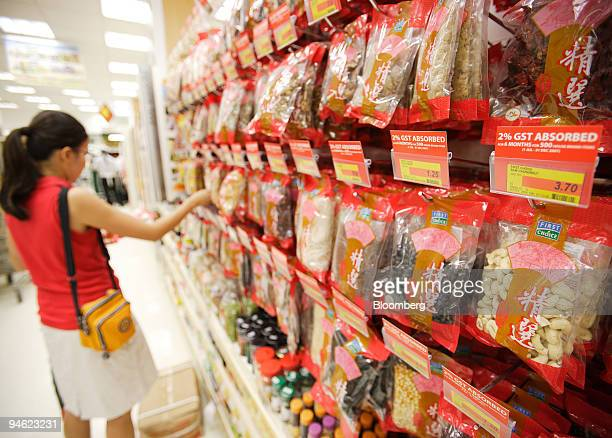 Supermarket price tags lure buyers with reduced goods and services tax or GST absorbed by the shop for some of their products in Singapore on Monday...