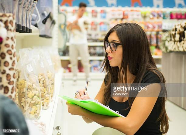 Supermercato Assistente alle vendite controlla i prodotti.  Cliente con cane sullo sfondo