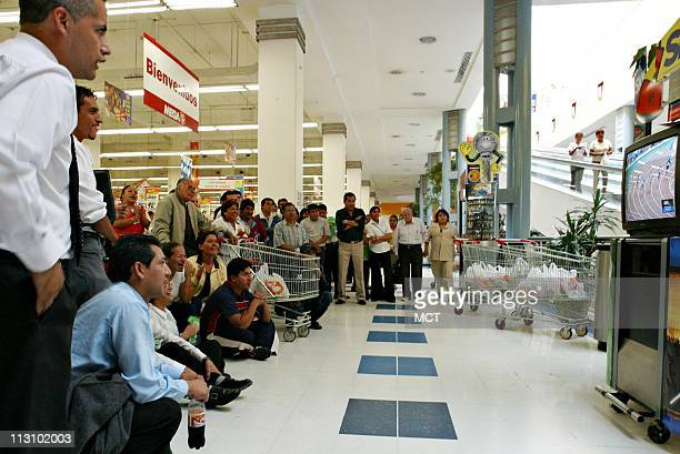 MEXICO CITY MEXICO Supermarket shoppers and workers watch Ana Gabriela Guevara compete in the 400 meter dash in Athens Greece on Tuesday August 24...