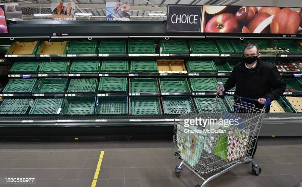 Supermarket shoppers walk past rows of empty shelves in Tescos on January 14, 2021 in Belfast, Northern Ireland. Supermarkets here are already seeing...
