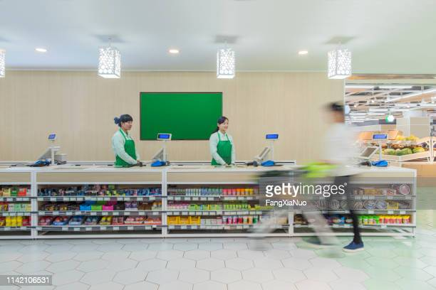 supermarket staff standing at check-out counter - till stock pictures, royalty-free photos & images