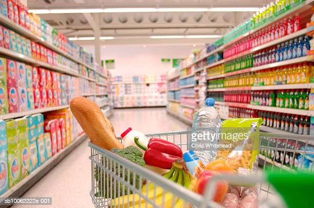 supermarket trolley filled with vegetables in aisle - shopping cart stock pictures, royalty-free photos & images