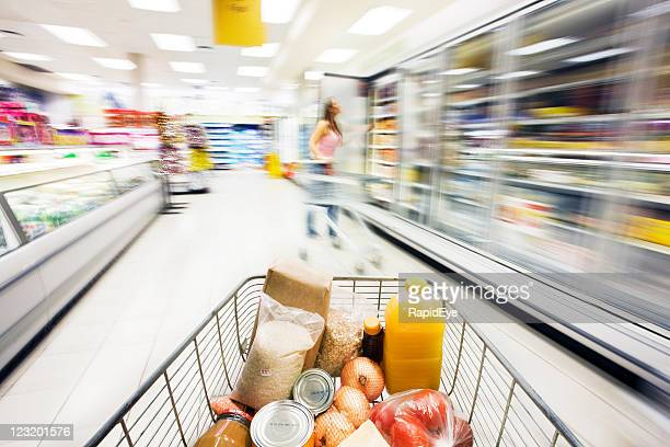 Supermarket trolley moves through fridge area showing motion blur