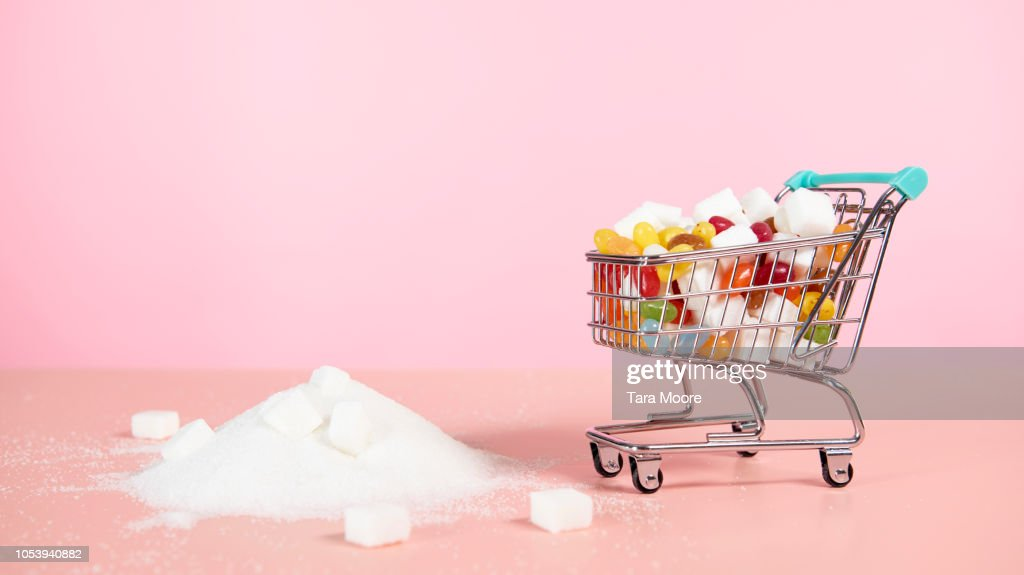 supermarket trolley with candy next to pile of sugar : Stock Photo