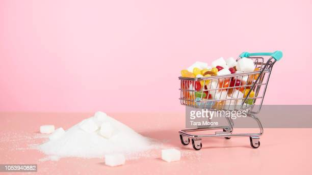 supermarket trolley with candy next to pile of sugar - sweet food stock pictures, royalty-free photos & images