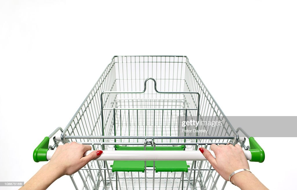 Supermarket trolley with woman's hands on white : Stock Photo