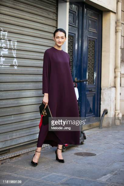Supermodel Ai Tominaga wears a purple dress and carries a black Valentino bag after the Valentino show during Couture Fashion Week Fall/Winter 2019...