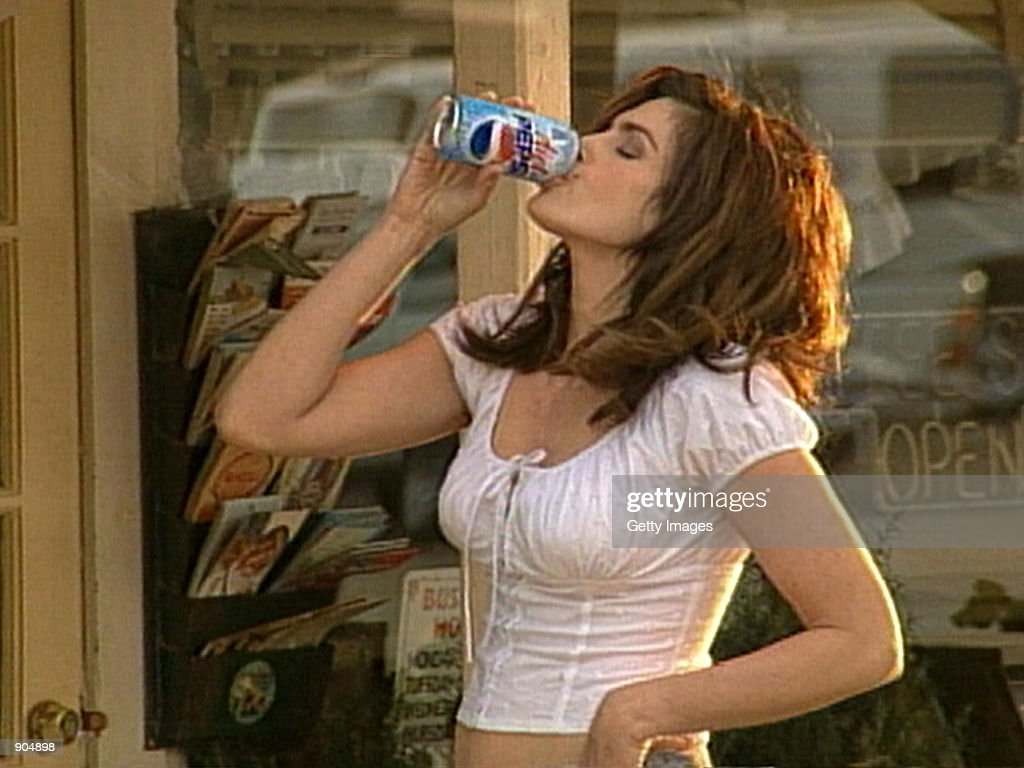 Supermodel Cindy Crawford drinks a Pepsi in this undated company supplied photograph. Crawford will star in a new Diet Pepsi commercial during the 74th Annual Academy Awards airing March 24, 2002 on ABC-TV. The new Diet Pepsi spot updates an award-winning ad produced for regular Pepsi in 1991, in which a pair of awestruck boys watched Crawford approach a Pepsi vending machine. In the new commercial, titled 'Two More Kids,' Crawford comes across a Diet Pepsi machine with sparkling new 'bubbly blue' graphics at a dusty old country store while the song 'Just One Look,' plays in the background.